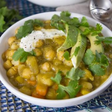 Vegetarian Chili Verde Stew in a white bowlwith avocado, sour cream, and cilantro