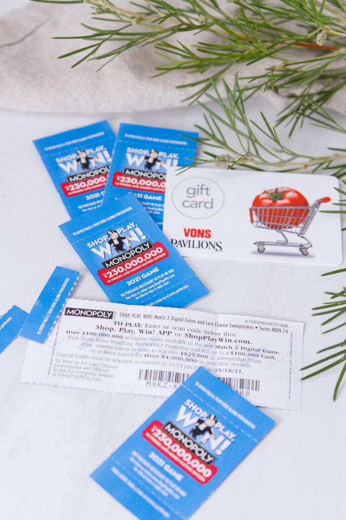 SHOP, PLAY, WIN!® game pieces with a Vons gift card and some greenery