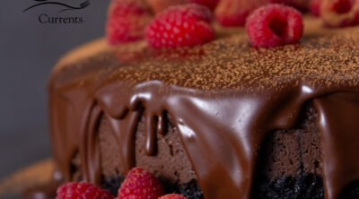 square crop of a whole Chocolate Raspberry Cheesecake garnished with raspberries and dripping with chocolate