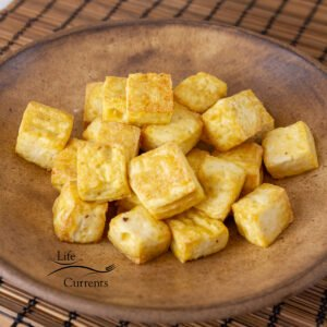 square crop of cooked tofu in a brown bowl.