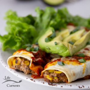 square crop of enchiladas on a plate with avocado slices and a salad