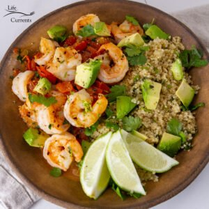 square crop of Seared Shrimp with Fresh Tomato Sauce and Cilantro Lime Quinoa top down view, served with lime wedges.