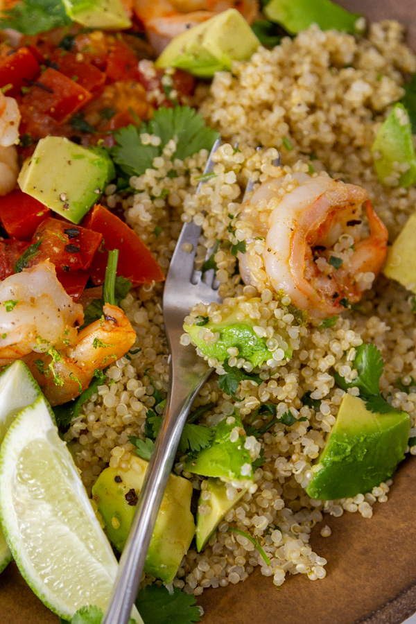 close up on fork in quinoa and shrimp bowl with veggies, served with lime wedges.