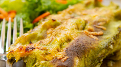 square crop of enchiladas on a plate with a salad and a fork.