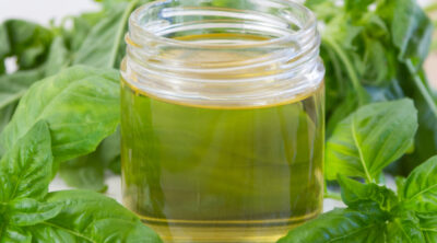 square crop of glass jar with basil syrup in it with fresh basil leaves.