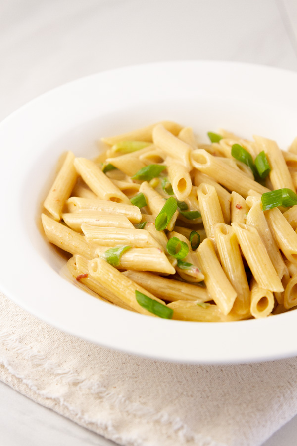 Creamy Peanut Noodles in a white bowl garnished with green onions.