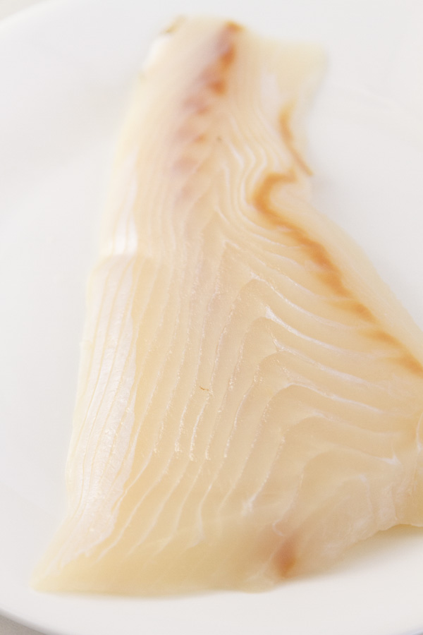 defrosted raw black cod on a plate.
