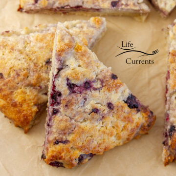 two blackberry scones stacked on parchment paper.