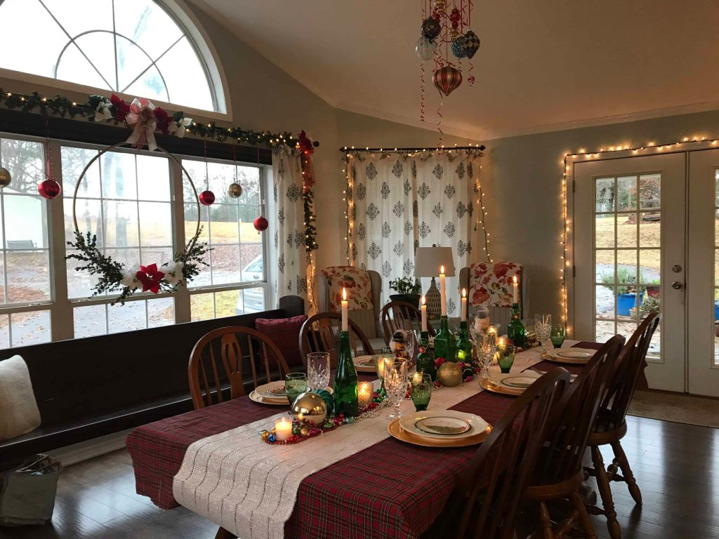 Dining room decorated with twinkle lights and candles for a Christmas table setting