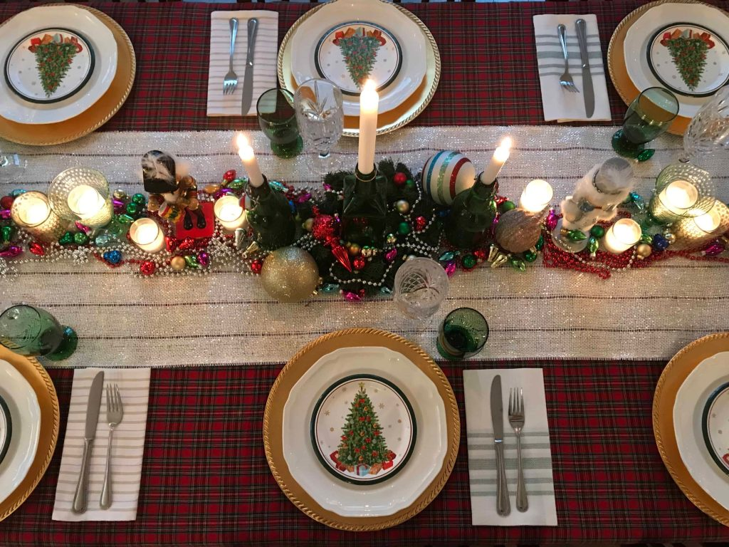 A Christmas table setting with a shimmering centerpiece studded with glowing candles, shimmering beads and ornaments
