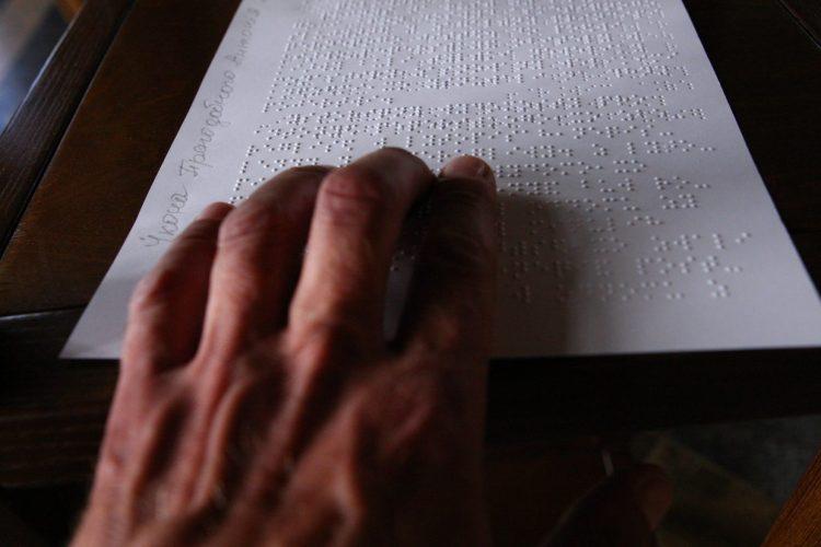 Рука и икона шрифтом Брайля