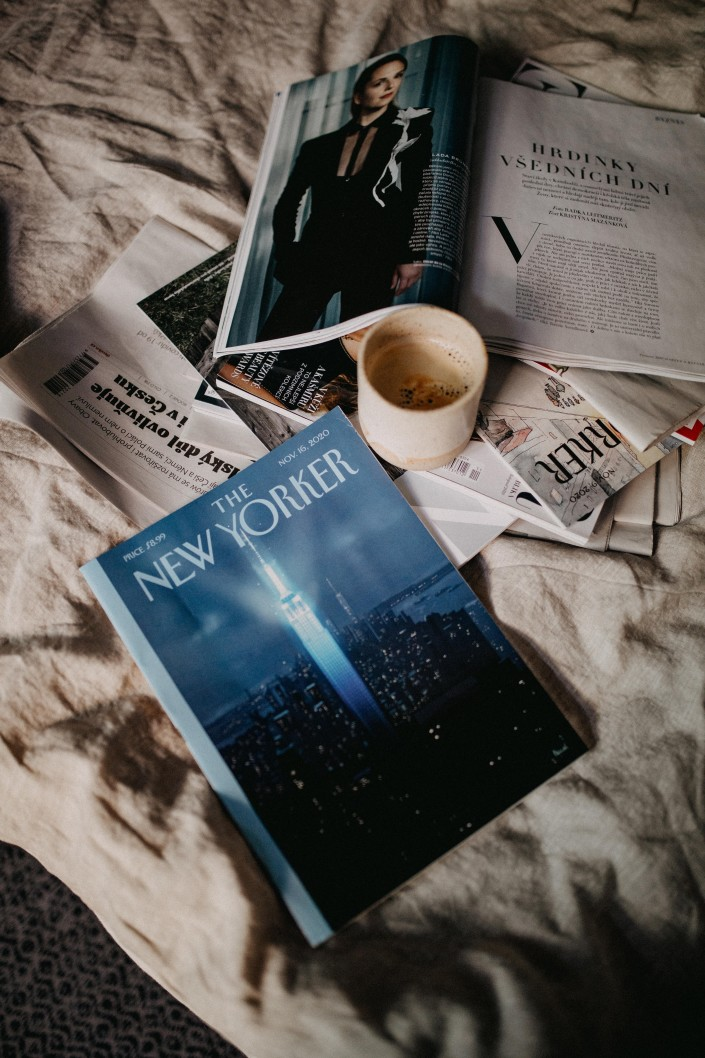magazines on bed while thinking on myths about productivity