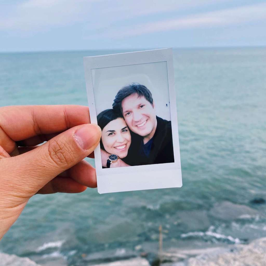 A polaroid picture of Mike and I being held up against a backdrop of the lake