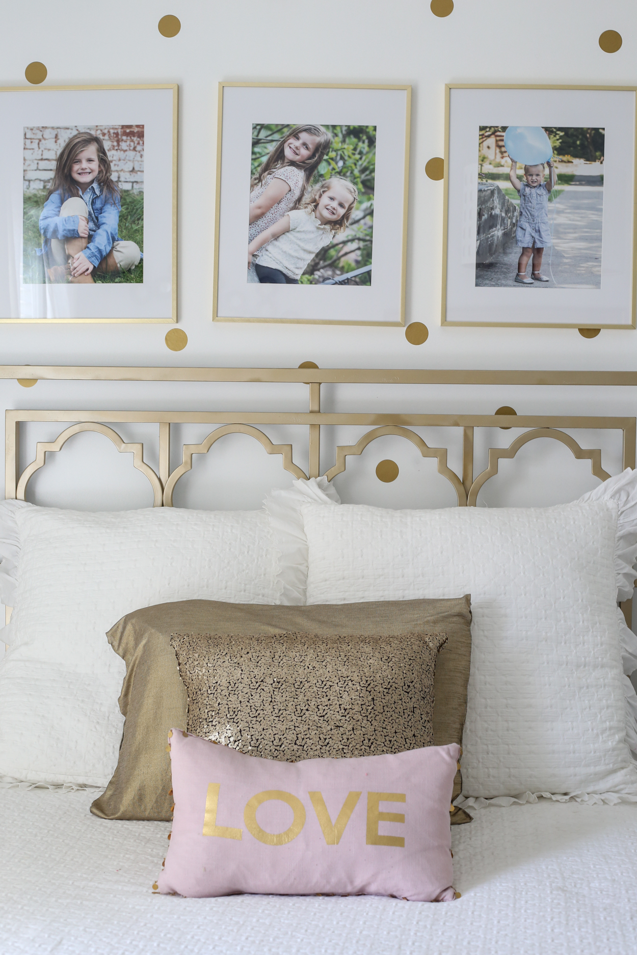 Bed frame with white pillows with three golden framed pictures.
