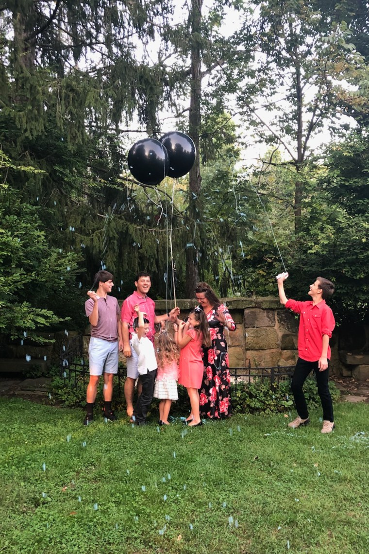 Family revealing gender reveal with popped balloons and blue sprinkles.