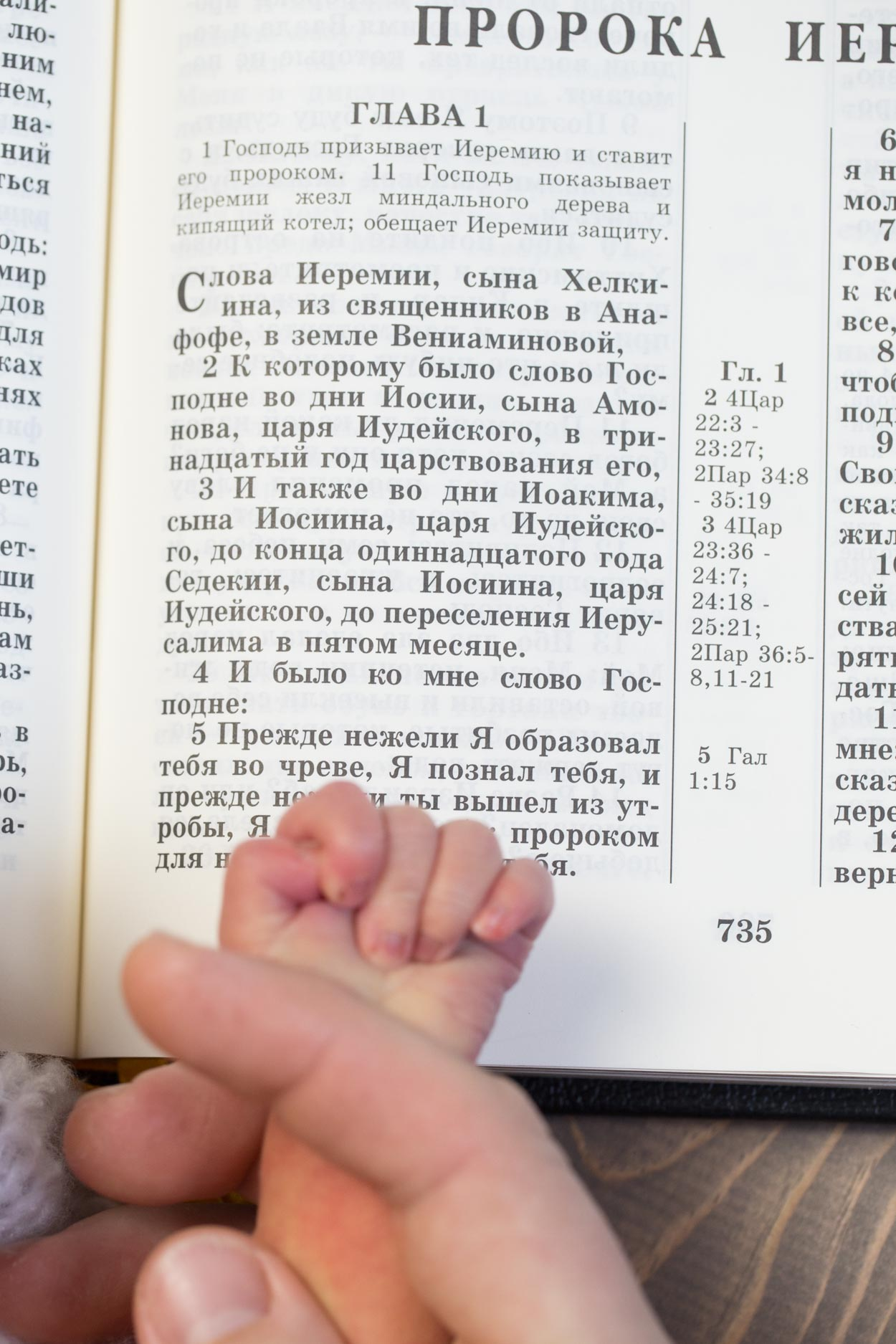 Baby hand held next to a bible.