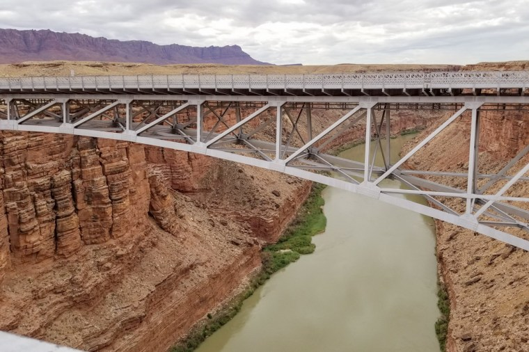 A bridge looking over a river and canyons.