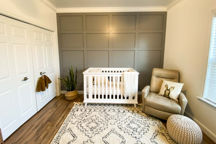 A wide view of the nursery with a crib, planter, and rocking chair.