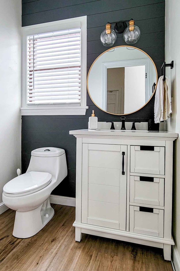 Powder room remodel with a small white vanity, toilet and two-light fixture.