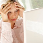 woman looking stressed at lap top