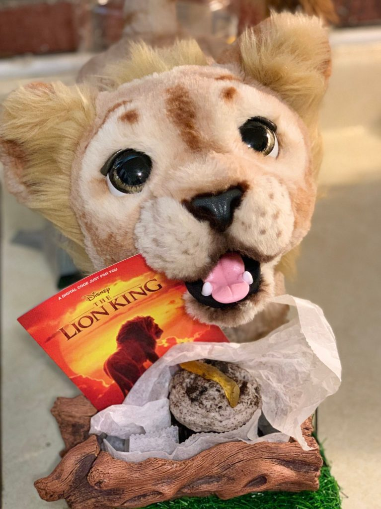 Baby Simba toy holding the Lion King Movie digital download.