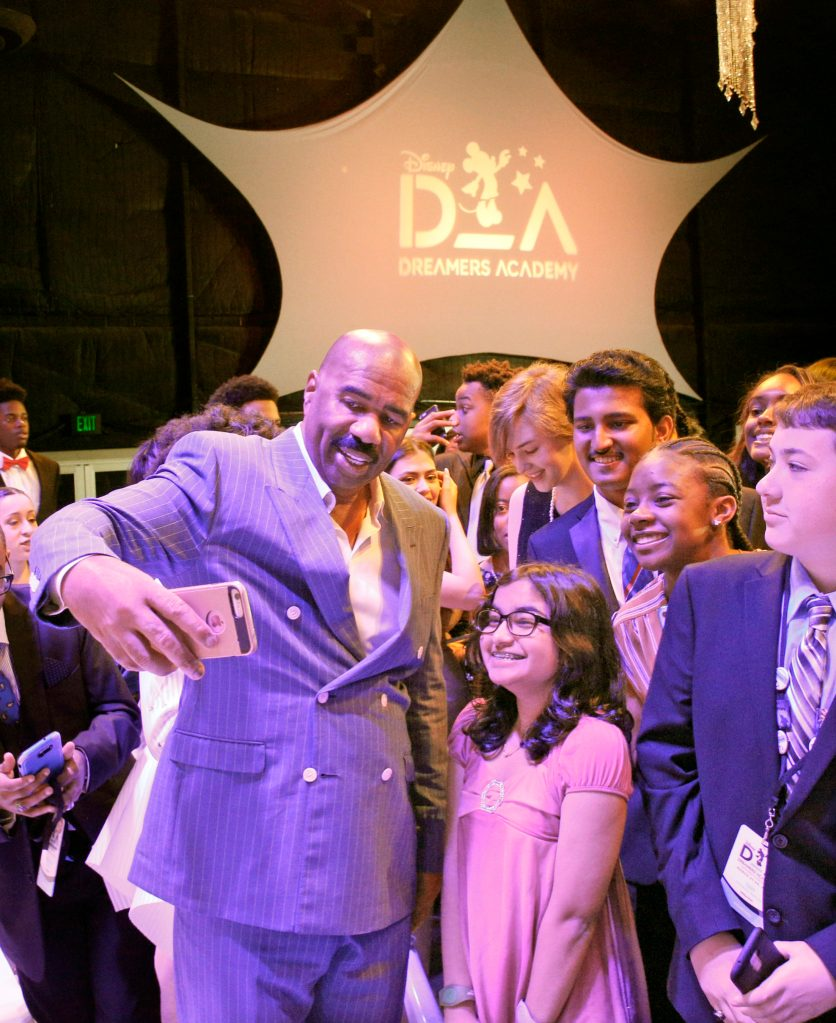 Steve Harvey taking selfies with some of the Disney dreamers.