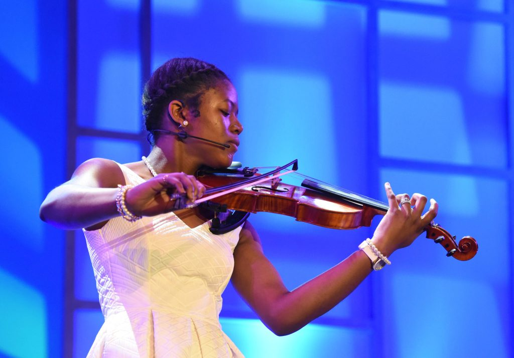 Teen attendee showing off her violin skills at Disney dreamers academy 2019
