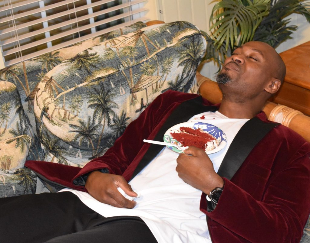 Brown Skin Male enjoying red velvet cake in a red velvet jacket in Myrtle Beach for thanksgiving