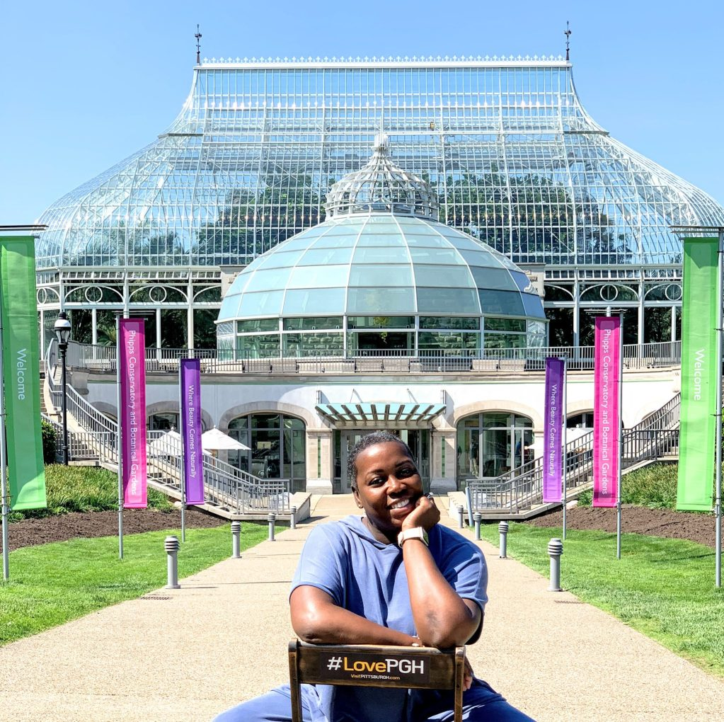 "Phipps Conservatory outside with ""pull up a chair"" featuring a brown girl."