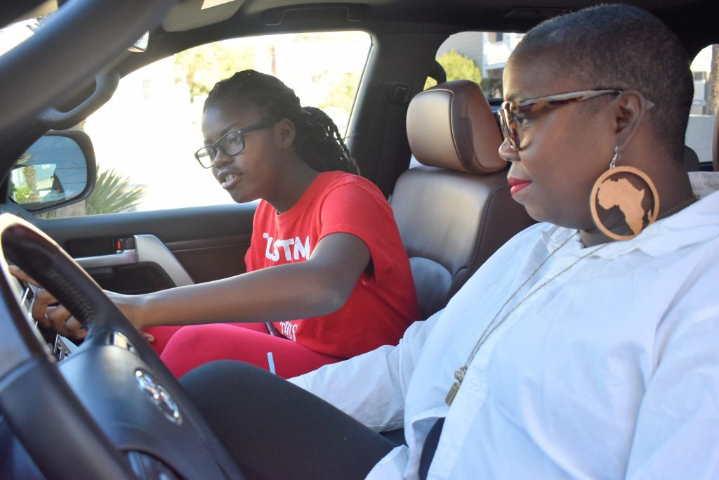 brown skin girls in the Toyota Landcruiser- what drives her