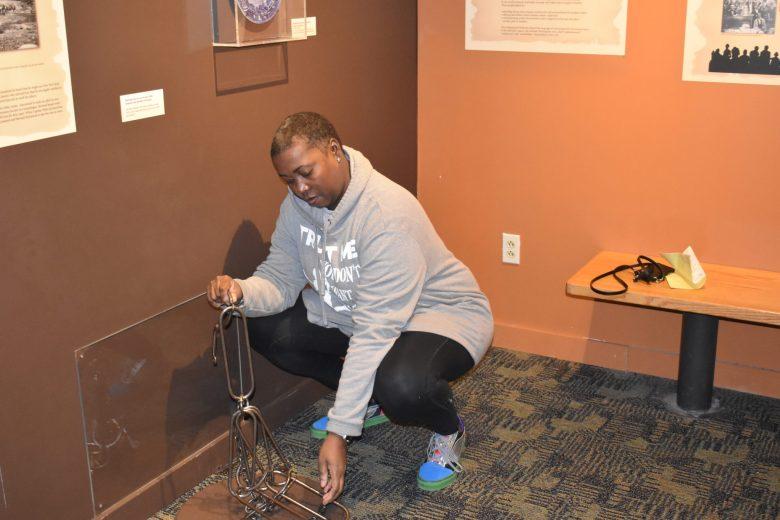 brown girl examining Rochester Museum Underground Railroad artifacts