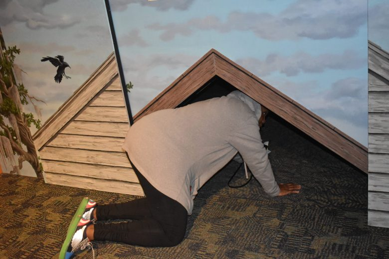 Brown girl checking out crawl space used for underground railroad in Rochester