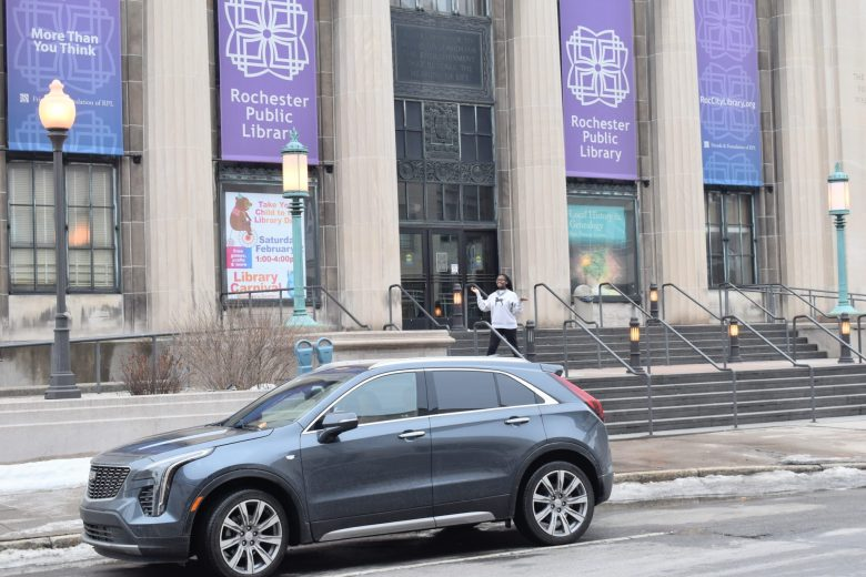 brown skin girl in front of Rochester public library with Cadillac XT5