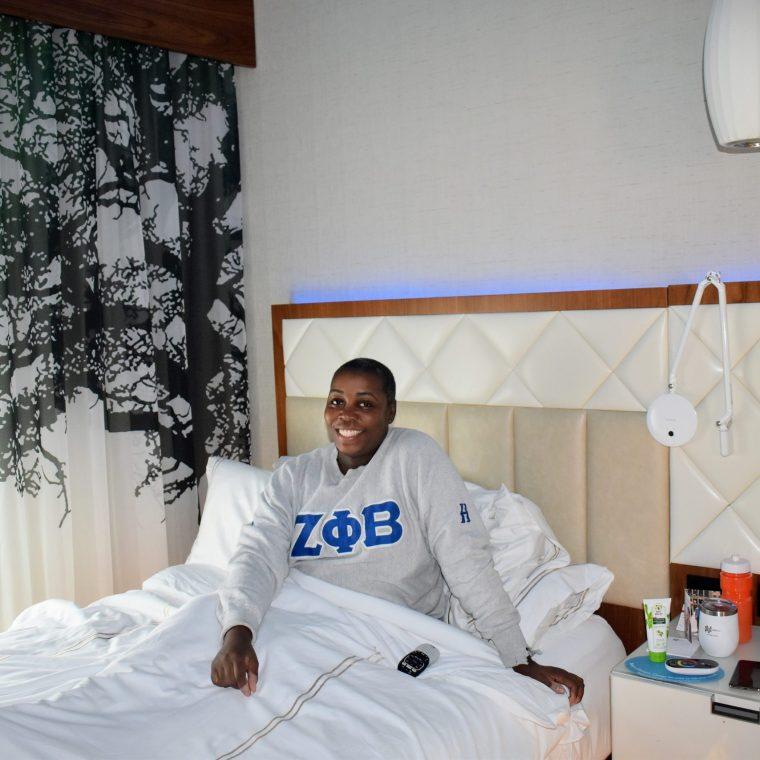 Zeta sorority girl traveling hotel bed smiling