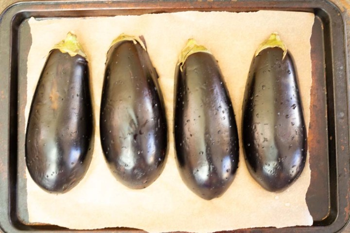 two fresh eggplants cut in half and placed on a baking sheet