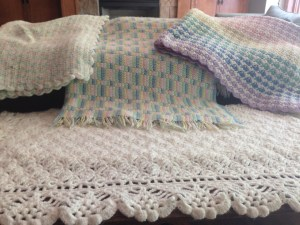 Left to right:  blanket I made in 4-H in elementary school, 2 blankets (before we knew the sex), and, in front, baptism blanket.