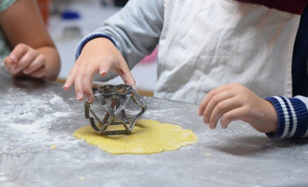 Children cutting out pastry shapes.