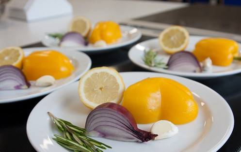 simple and delicious ingredients on a plate. Peppers, onions, lemon, garlic and roemary.