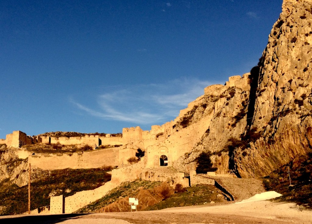 Ancient ruin of Acrocorinth on top of the mountain surrounded by rocks with a bright blue sky