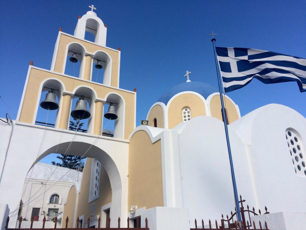 White washed church with its blue dome and 6 bells in a pyramid shape and the Greek flag flying in front.