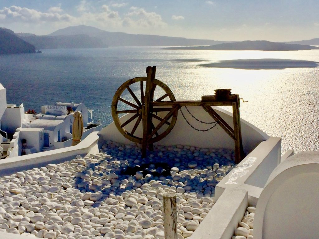 Overlooking a bicycle type feature towards the blue sea from the town of Oia surrounded by white washed buildings