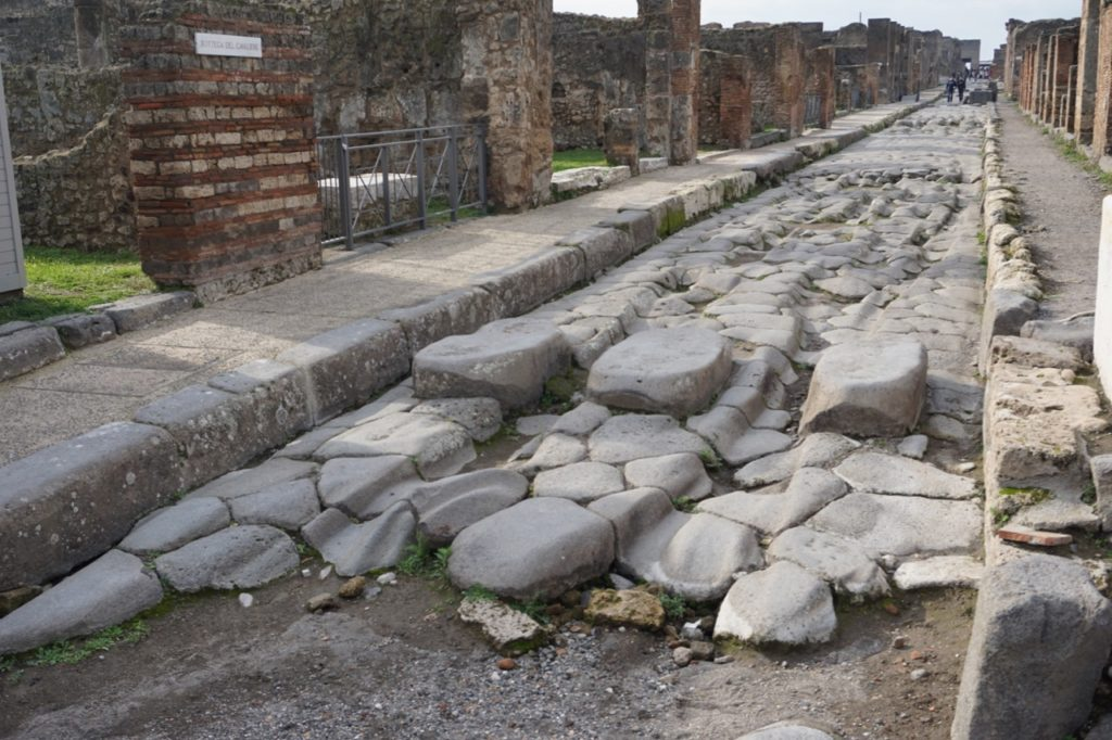 Cobble stones with ruts carved into them along with large stones on the road for people to walk on to cross the road