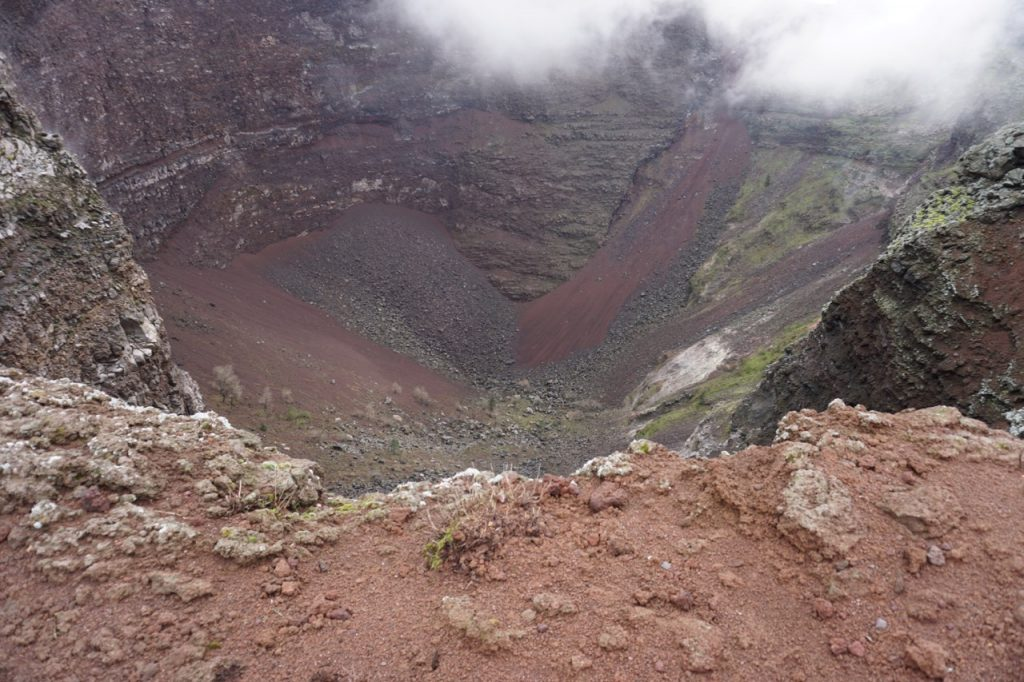 An invertedd conical shaped crater with redd-ish brown and grey earth coloured stones with a hint of green near the bottom