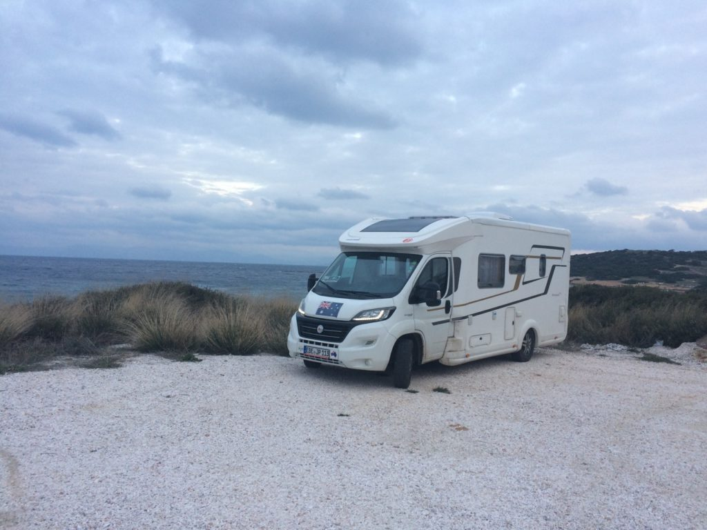 White campervan parked close by the sea