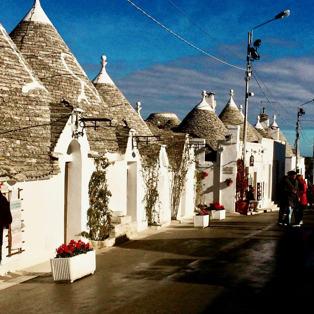 A street front showing the small trulli cone shaped grey stoned roofs - with white pinnacles on the top and symbols painted on the roofs in Alberobello