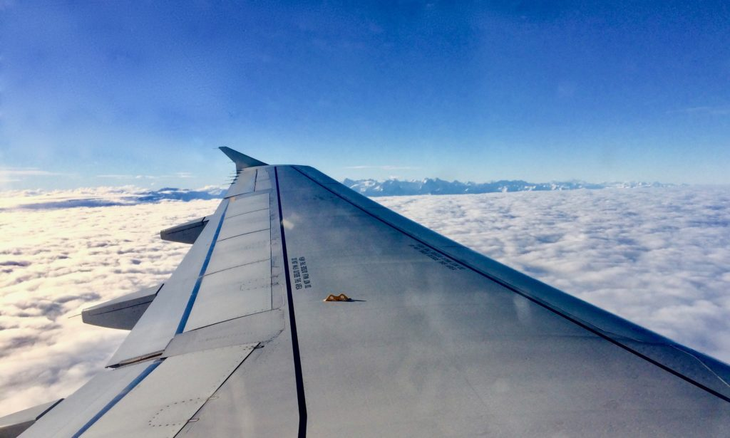 aeroplane wing above the white clouds with the swiss mountains in the distance