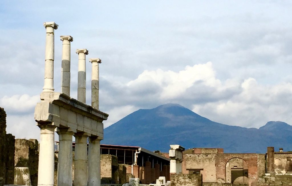 Old ruins of Pompeii in the foreground with the dark mountain of Mt Vesuvius in the background