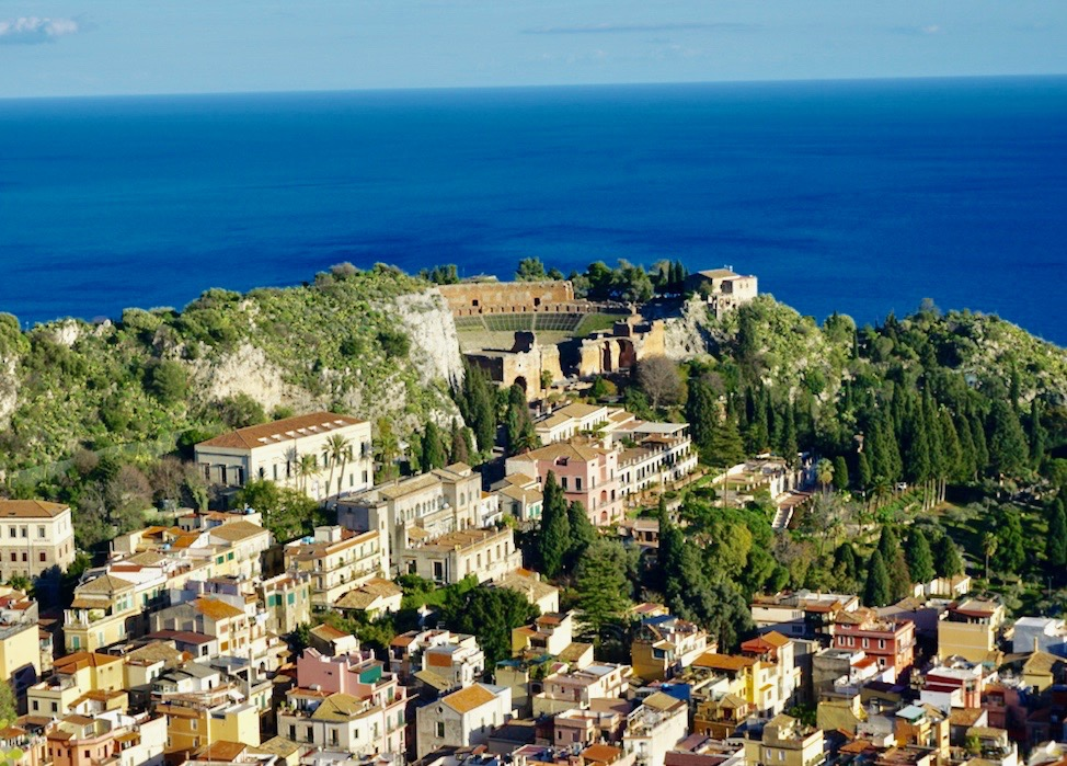 Taormina with its Ancient Greek theatre in the background and the blue sea behind all of this