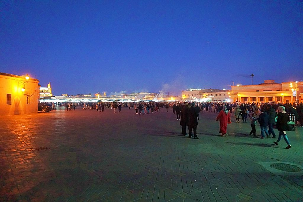 Large brightly lit square with many people flocking towards it