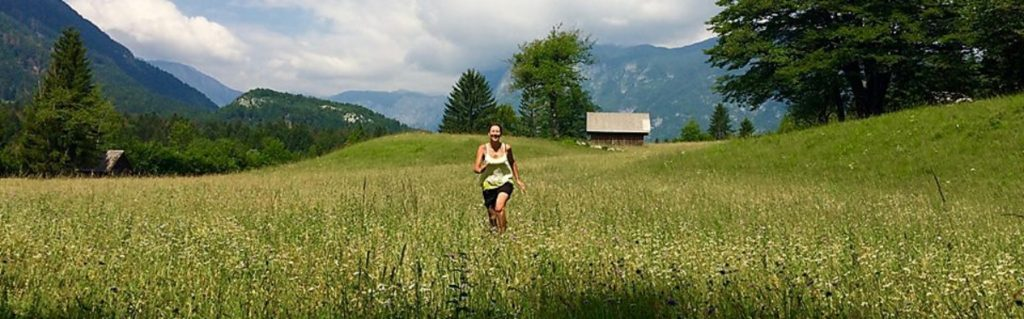 girl running in the middle of a filed with trees and mountains in the background
